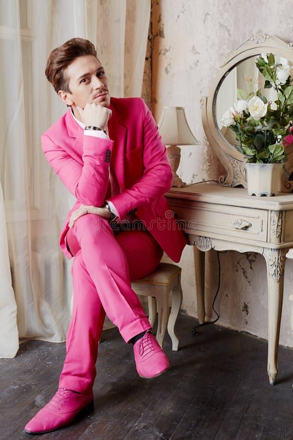 Junger Mann Sitzt Auf Stuhl Mit Den Gekreuzten Beinen