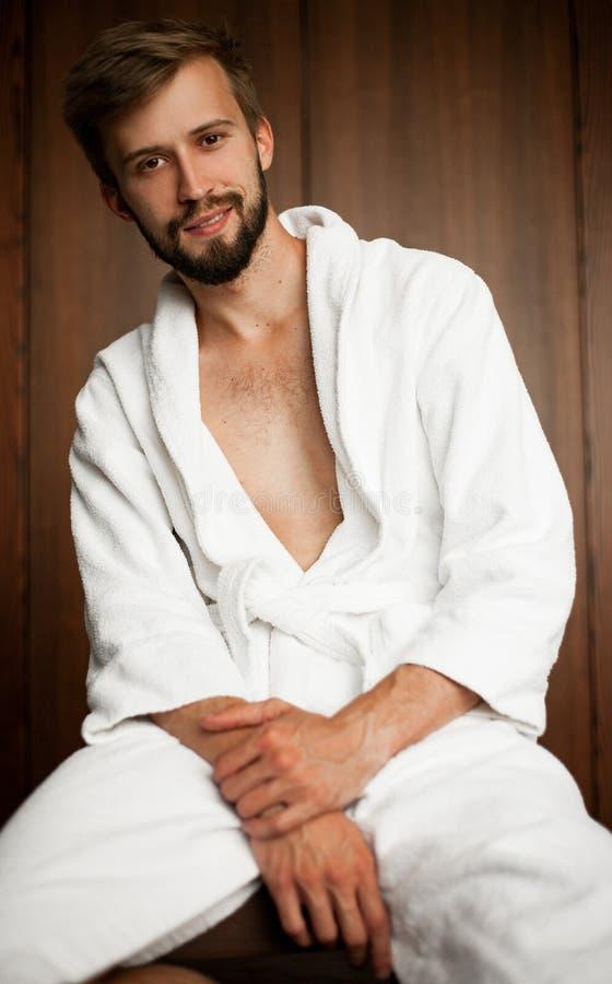 Junger Mann sitzt im Bademantel auf braunem Hintergrund stockbilder