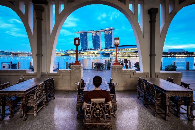 Junger Mann sitzt und genießt die Ansicht von Jachthafenbuchtsanden, Singapur lizenzfreies stockfoto