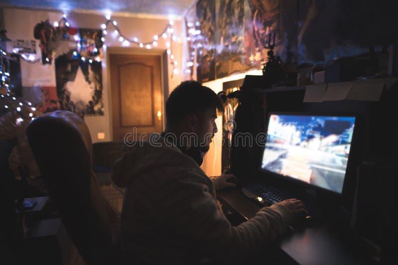 Junger Mann sitzt zu Hause in seinem Raum und spielt Spiele auf einem Computer Spiel des Rennens auf dem Computer lizenzfreies stockfoto