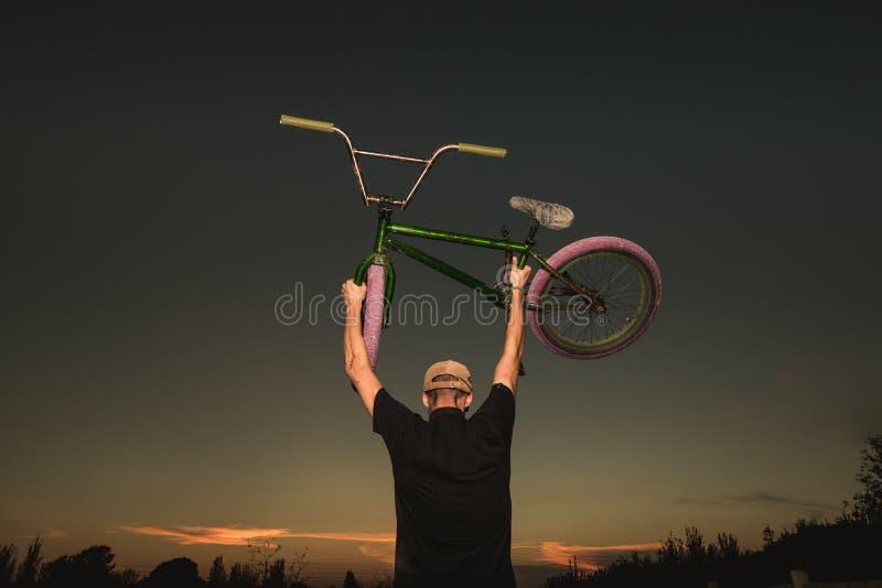Junger Mann stehendes bmx Fahrrad BMX-Reiter mit und ein Sonnenuntergang lizenzfreies stockbild