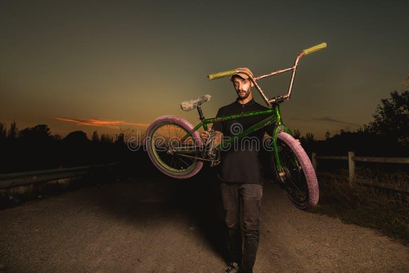 Junger Mann stehendes bmx Fahrrad BMX-Reiter mit und ein Sonnenuntergang stockfotografie