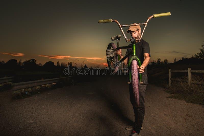 Junger Mann stehendes bmx Fahrrad BMX-Reiter mit und ein Sonnenuntergang lizenzfreie stockfotografie