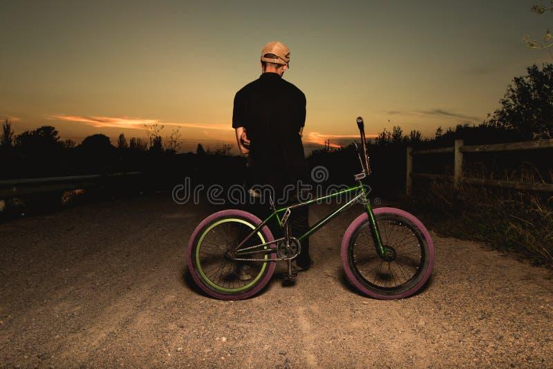 Junger Mann stehendes bmx Fahrrad BMX-Reiter mit und ein Sonnenuntergang stockfotos