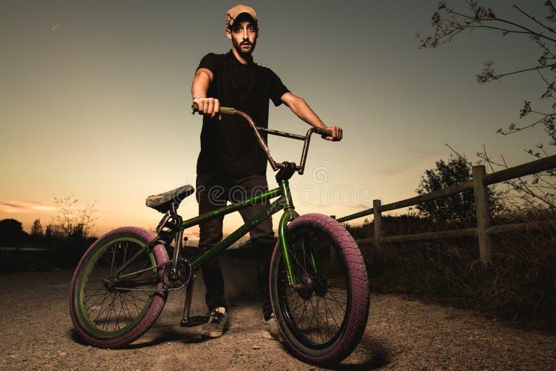 Junger Mann stehendes bmx Fahrrad BMX-Reiter mit und ein Sonnenuntergang stockbilder