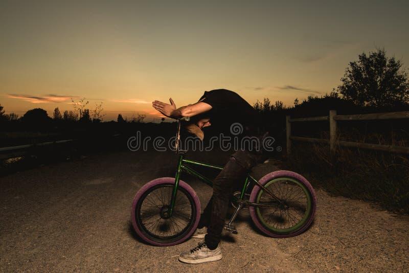 Junger Mann stehendes bmx Fahrrad BMX-Reiter mit und ein Sonnenuntergang lizenzfreie stockbilder