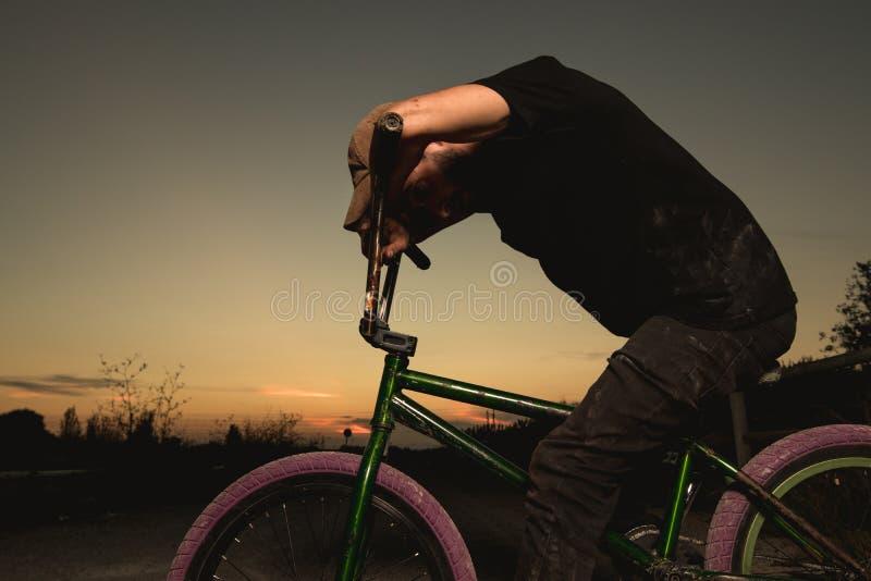 Junger Mann stehendes bmx Fahrrad BMX-Reiter mit und ein Sonnenuntergang stockbild