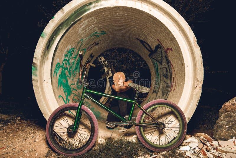 Junger Mann stehendes bmx Fahrrad BMX-Reiter mit und ein Sonnenuntergang lizenzfreies stockfoto