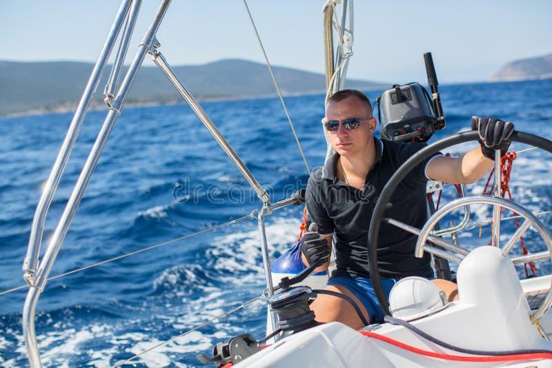 Junger Mann steuert ein Segeljachtboot in der hohen See sport lizenzfreies stockfoto