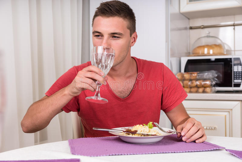 Junger Mann-Trinkwasser mit Abendessen lizenzfreies stockbild