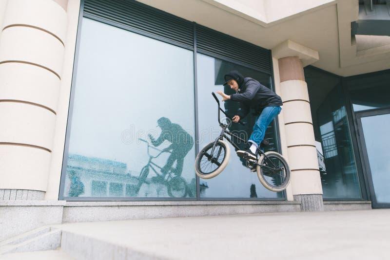 Junger Mann tut Tricks auf BMX gegen den Hintergrund der Architektur Ein Junge springt auf ein BMX-Fahrrad lizenzfreie stockfotografie