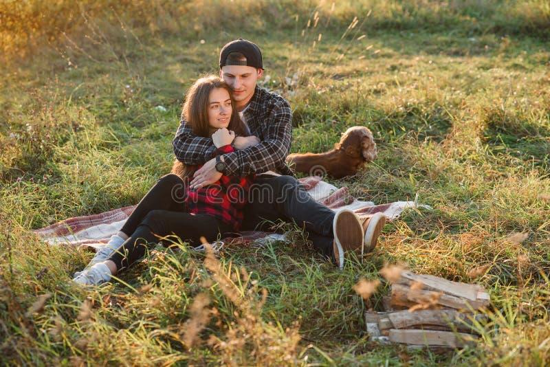 Junger Mann umarmt zart seine hübsche Freundin Junges Paar sitzt auf dem Plaid am grünen Rasen bei Sonnenuntergang lizenzfreie stockfotos