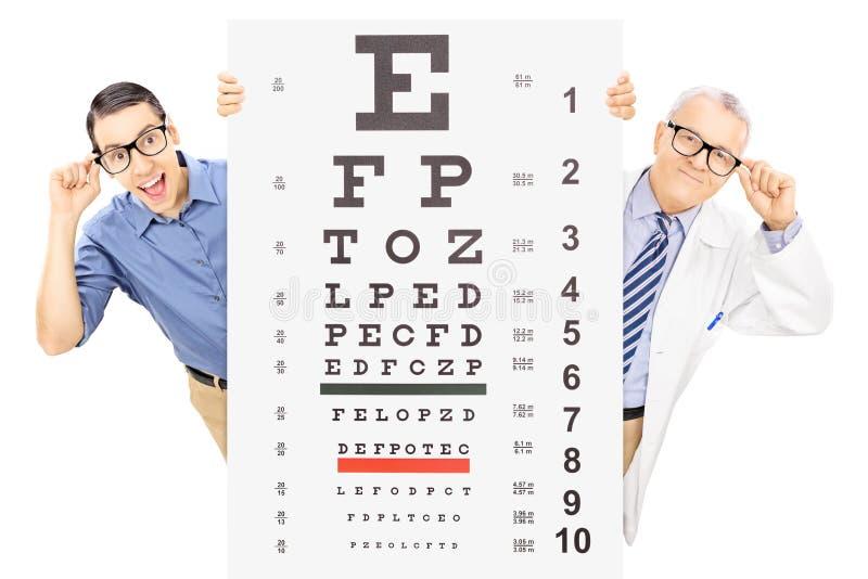 Junger Mann und ein Optiker mit den Gläsern, die hinter Sehvermögen stehen stockfoto