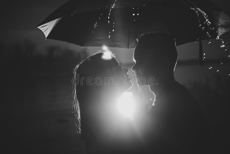Junger Mann und Frau des schwarzen weißen Fotos unter einem Regenschirm und einem Regen lizenzfreie stockfotografie