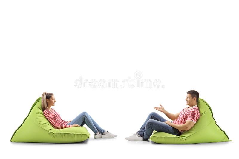 Junger Mann und Frau, die auf Bohnentaschen und -unterhaltung sitzt stockfoto