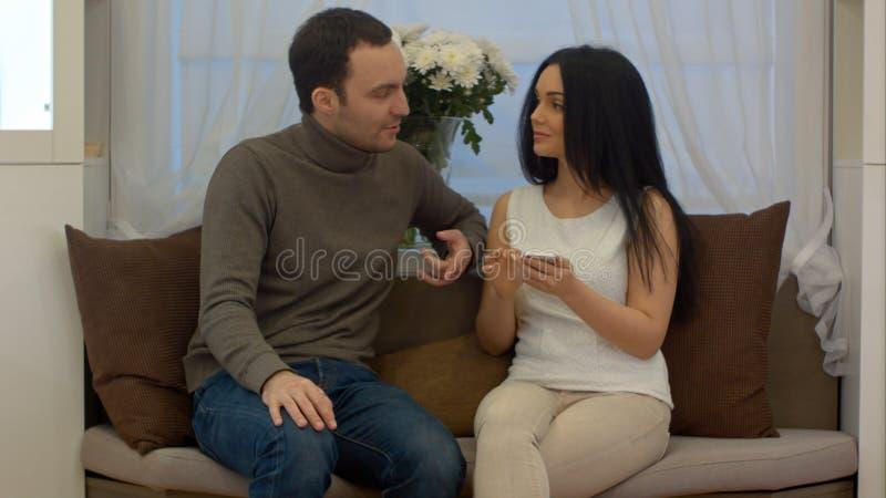 Junger Mann und Frau, die auf Sofa im Wohnzimmer sitzt und etwas auf Schirm des intelligenten Telefons bespricht stockbilder