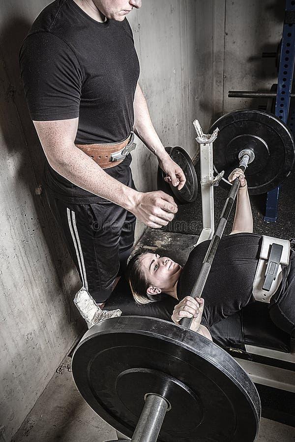 Junger Mann und Frau, die in einer kiesigen Kellerturnhalle powerlifting ist stockbild