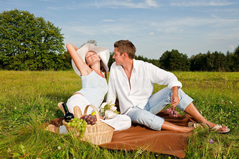 Junger Mann und Frau, die Picknick in der Wiese hat lizenzfreies stockfoto