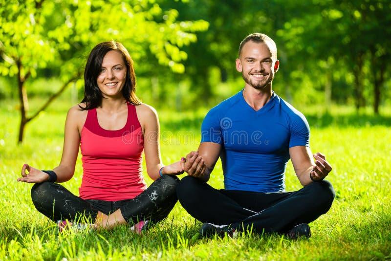Junger Mann und Frau, die Yoga im sonnigen Sommer tut stockfotos