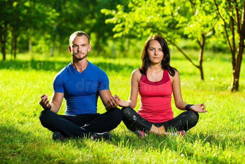 Junger Mann und Frau, die Yoga im sonnigen Sommer tut lizenzfreie stockfotografie