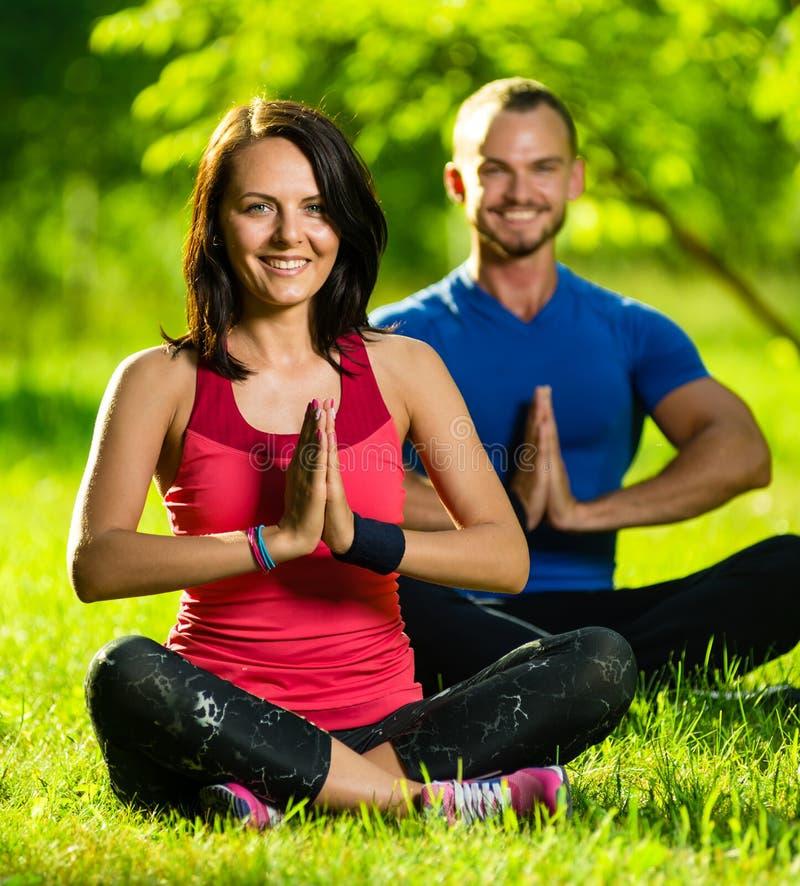 Junger Mann und Frau, die Yoga im sonnigen Sommer tut lizenzfreie stockbilder