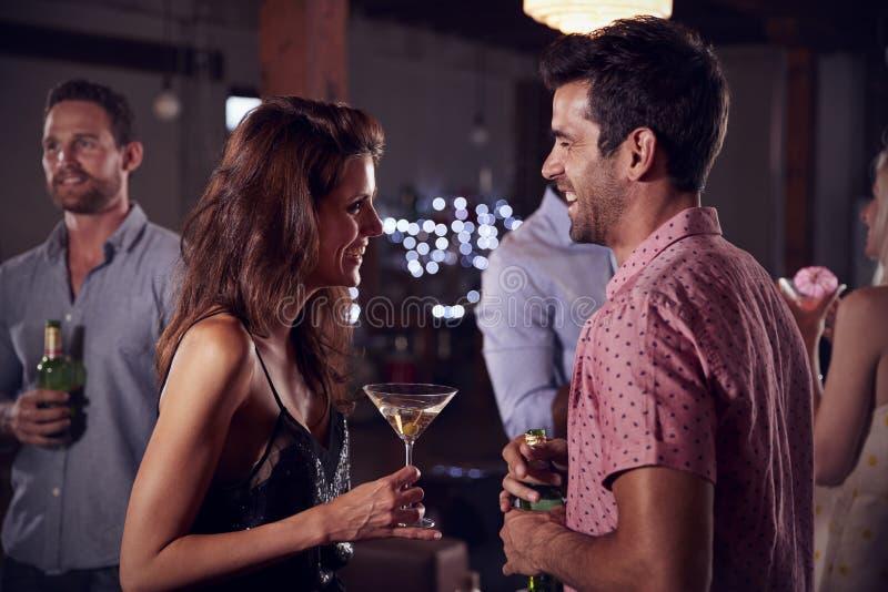 Junger Mann und Frau sprechen und lachen über eine Partei, Seitenansicht lizenzfreies stockbild