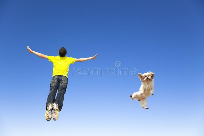 Junger Mann und Hund, die in den Himmel springt lizenzfreie stockfotos