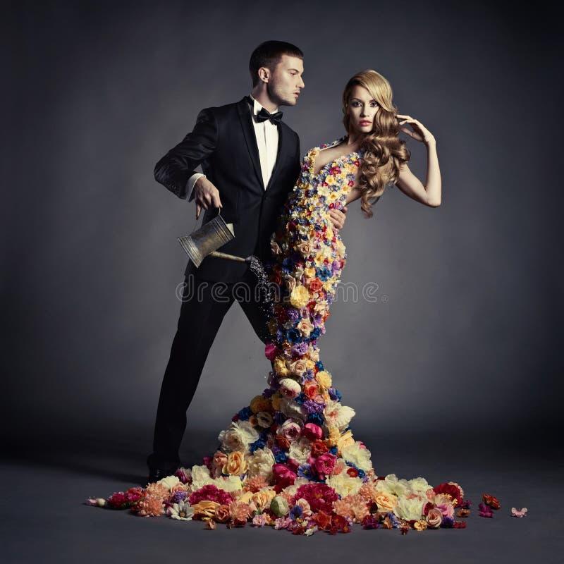 Junger Mann und schöne Dame in der Blume kleiden an