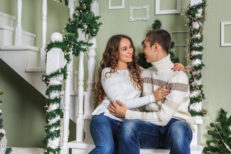 Junger Mann und seine Freundinumarmung, die auf den Schritten am Vorabend der Weihnachtsfeiertage sitzt lizenzfreies stockfoto