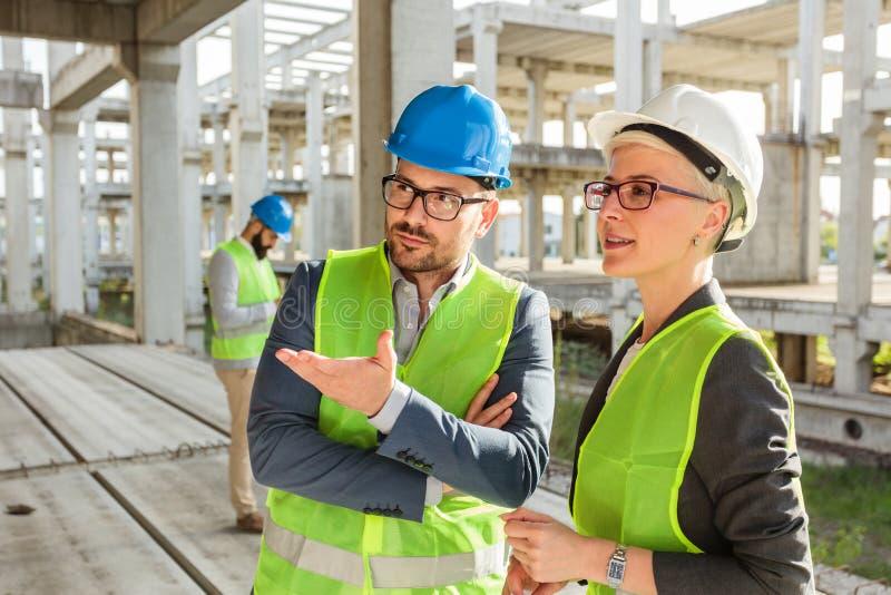 Junger Mann und weibliche Architekten oder Teilhaber, die auf einer Baustelle sprechen und sich besprechen lizenzfreie stockfotos