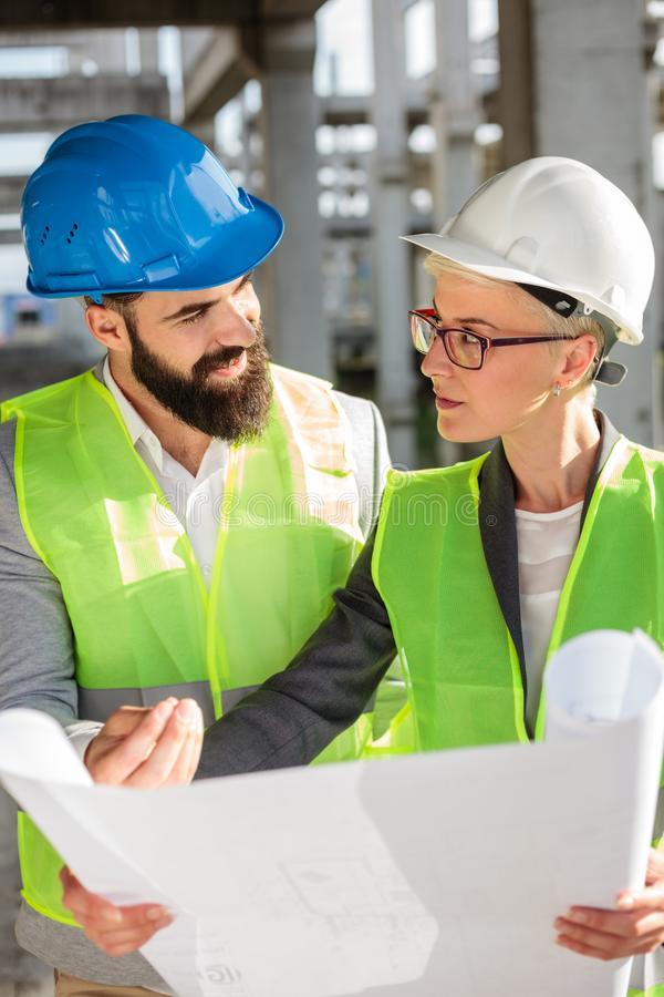 Junger Mann und weibliche Architekten oder Teilhaber, die Grundrisse auf einer Baustelle, gegenüberstellend besprechen lizenzfreies stockfoto