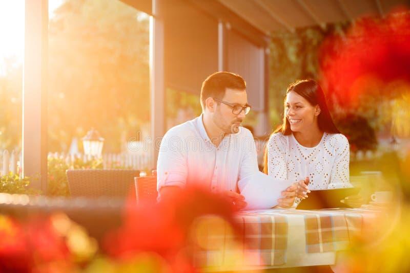 Junger Mann und weibliche Geschäftsleute, die eine zufällige Arbeitssitzung in einem Flussufercafé haben stockbilder