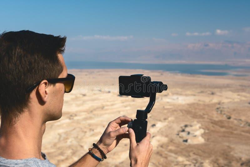 Junger Mann unter Verwendung des Kardanrings in der Wüste von Israel stockfotografie