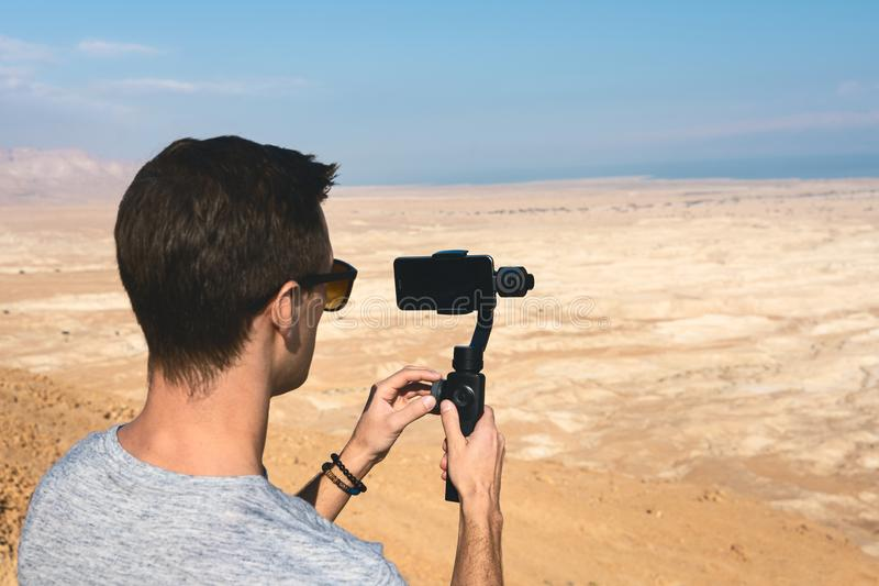 Junger Mann unter Verwendung des Kardanrings in der Wüste von Israel lizenzfreie stockbilder