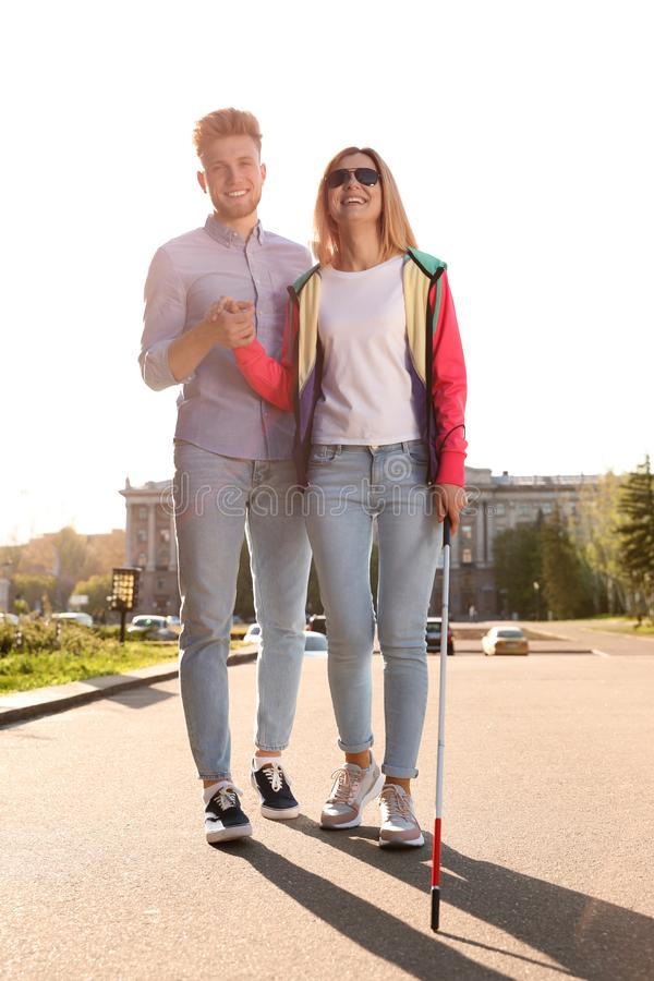 Junger Mann, welche blinder Person mit dem langen Stockgehen hilft stockfotografie