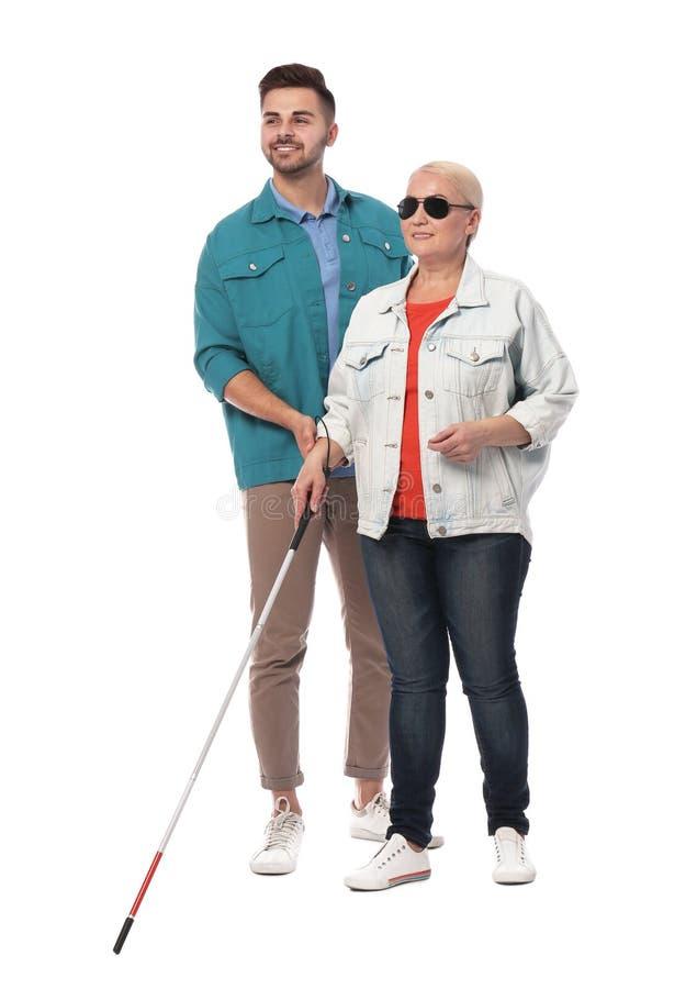 Junger Mann, welche blinder Person mit langem Stock auf Weiß hilft lizenzfreie stockfotos