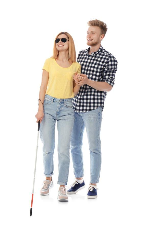 Junger Mann, welche blinder Person mit langem Stock auf Weiß hilft stockfotografie