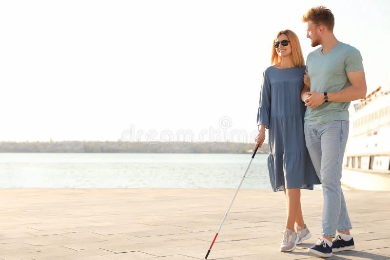 Junger Mann, welche blinder Person mit langem Stock in der Stadt hilft lizenzfreies stockfoto