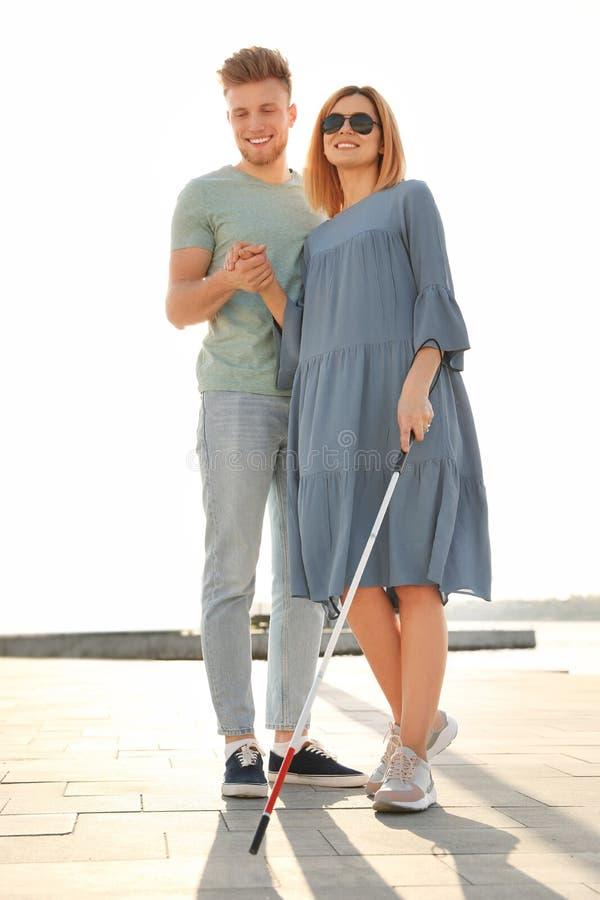 Junger Mann, welche blinder Person mit langem Stock hilft lizenzfreie stockbilder