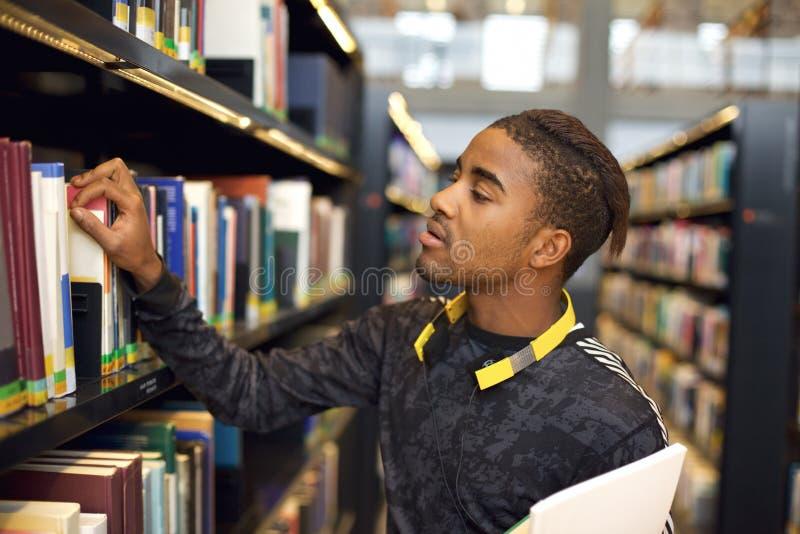 Junger Mann, welche nach Büchern an der öffentlichen Bibliothek sucht stockbild