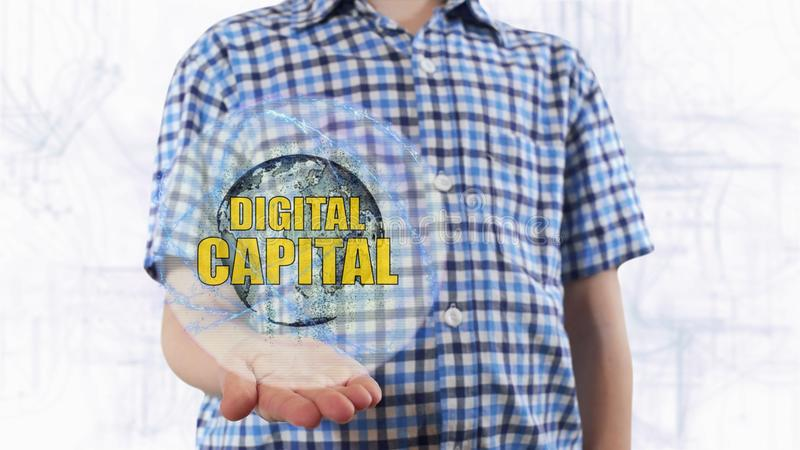 Junger Mann zeigt ein Hologramm des Planetenerd-und -textdigital-Kapitals stockfoto