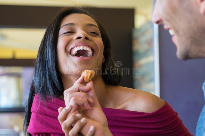 Junger Mann zieht seine Freundin mit Hörnchen ein stockfoto