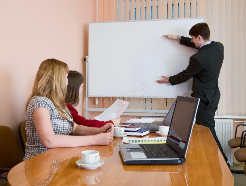 Junger Mann, zum bei einer Sitzung zu sprechen stockbild
