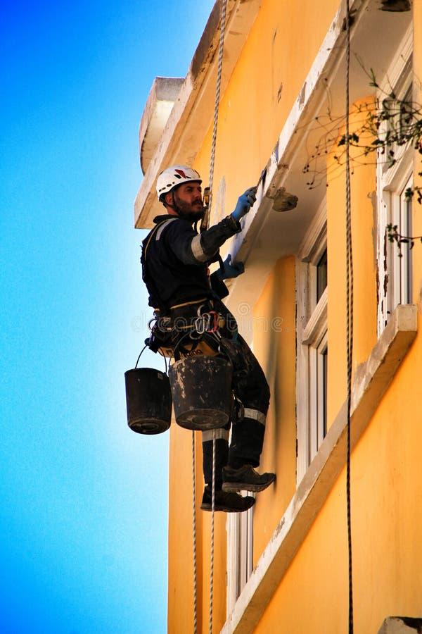 Junger Maurerbergsteiger, der Reparaturarbeit in einer Fassade von Lissabon erledigt stockfotos