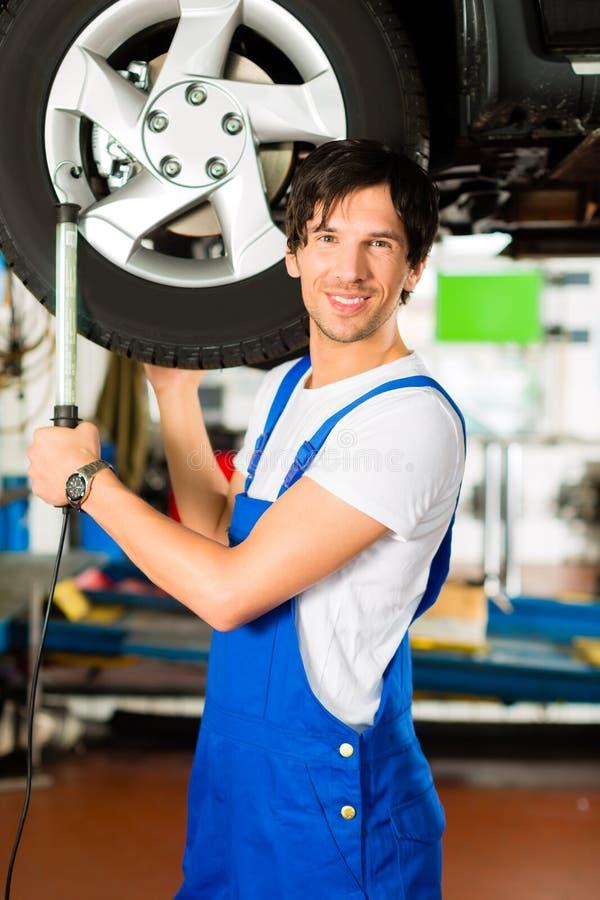 Junger Mechaniker in der blauen Gesamtfunktion auf Auto stockbilder
