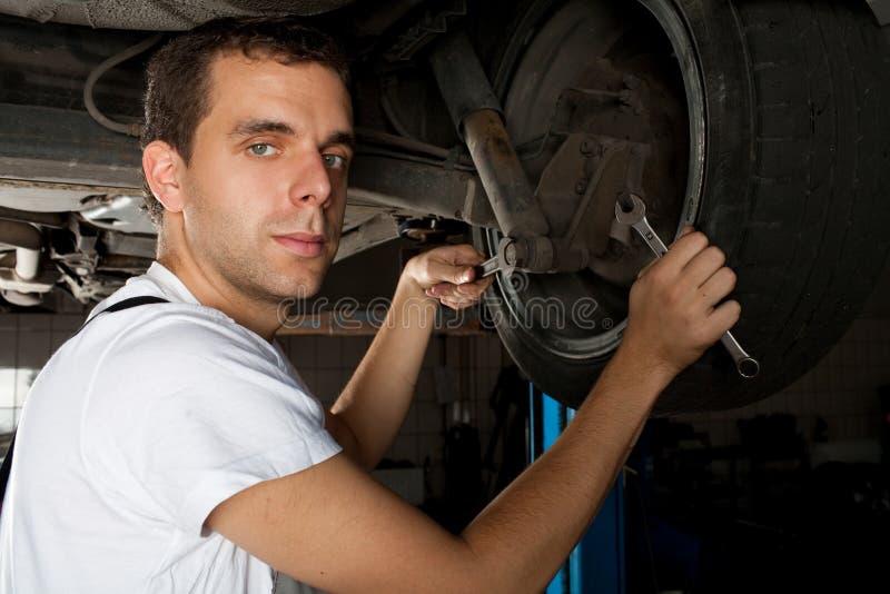 Junger Mechaniker, der unter Auto arbeitet stockfoto