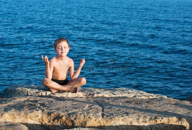 Junger meditierender Junge lizenzfreie stockfotos
