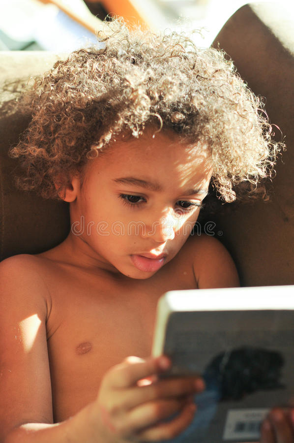Junger Mischrassejunge mit Lesung des gelockten Haares stockbild