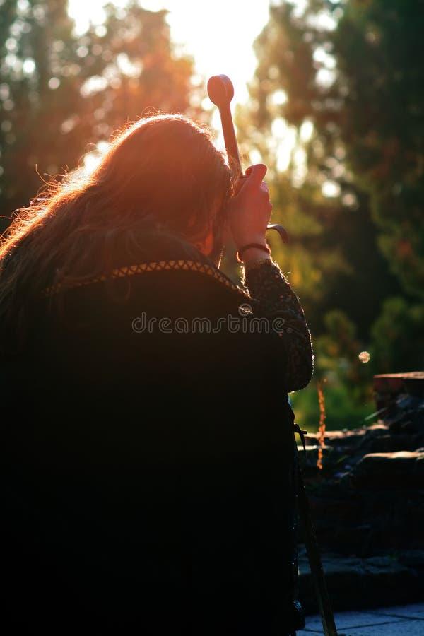 Junger mittelalterlicher Prinz mit Säbel und schwarzem Umhang lizenzfreies stockfoto