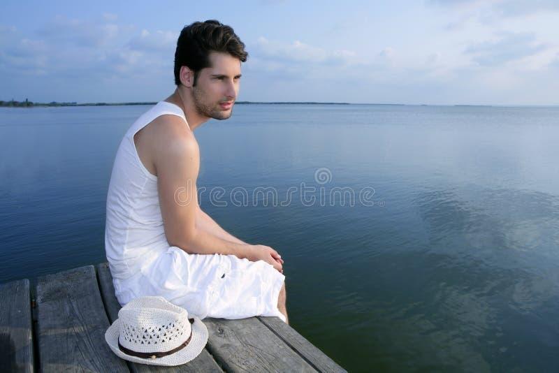 Junger Mittelmeermann entspannte sich auf hölzernem Pier stockbild